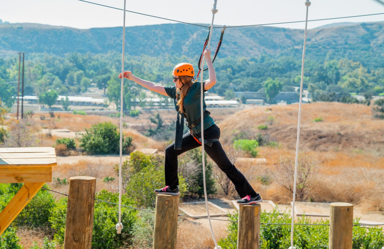 Crossing bridge of vertical wooden poles on the Adventure Hill course