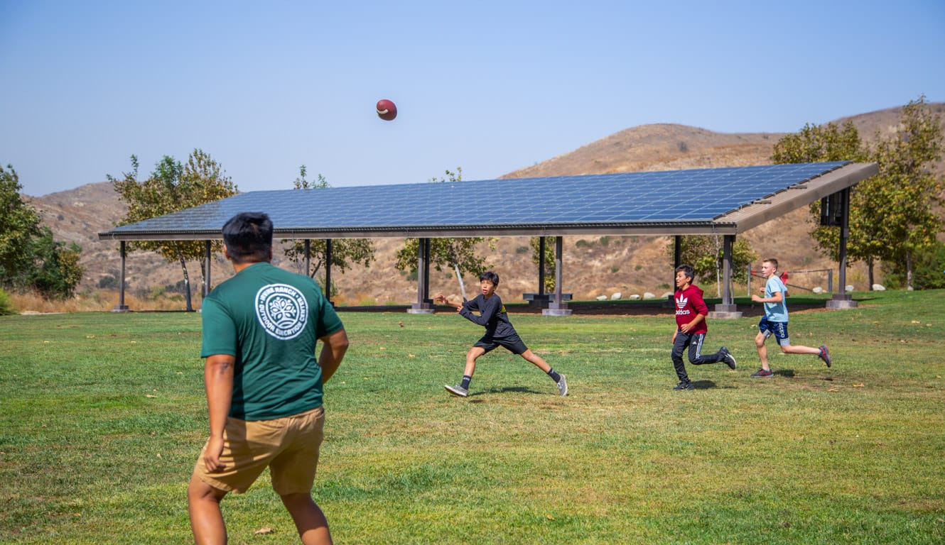 Boys playing football with staff