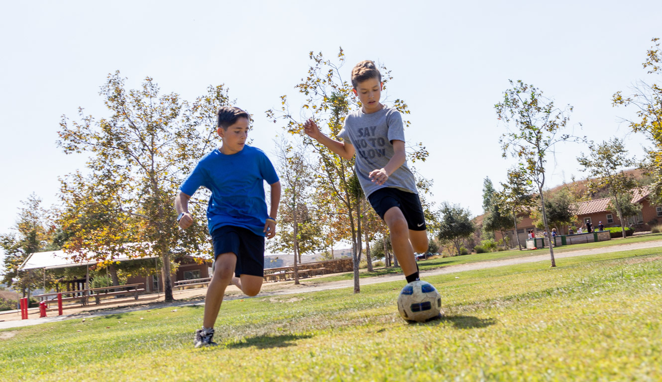 Two boys playing soccer on field at Irvine Ranch