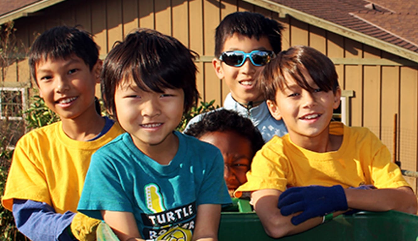 Kids smiling by recycling bin at Irvine Ranch's Day of Service