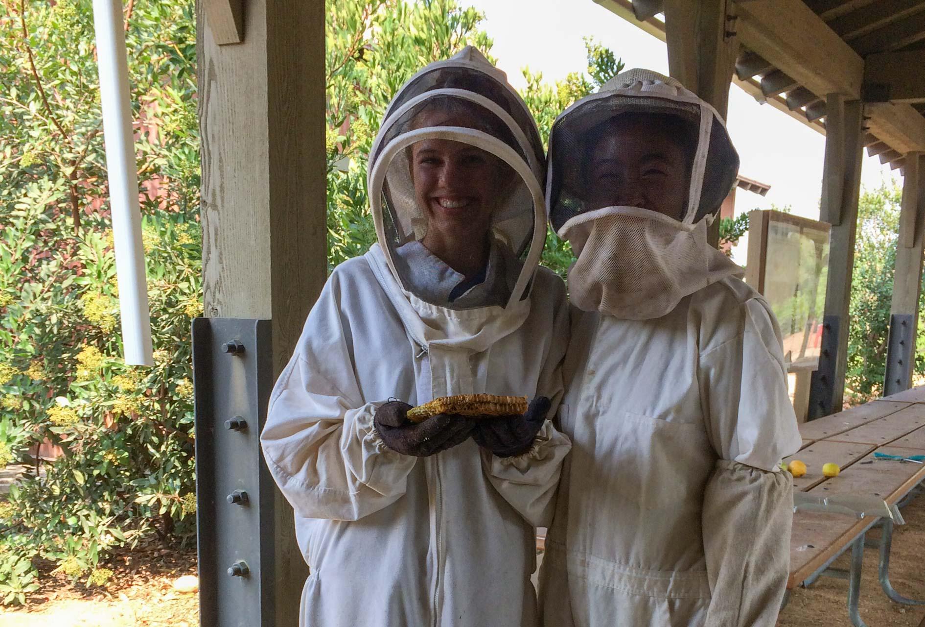 Two teens dressed in beekeeper gear volunteering