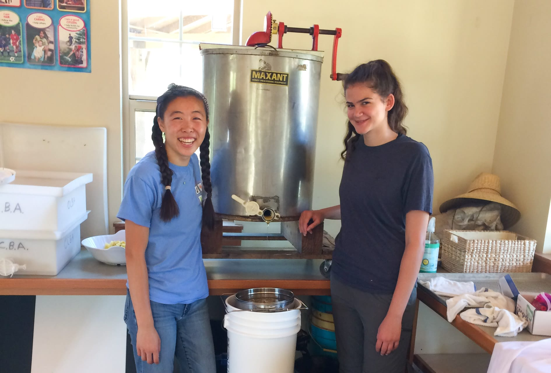 Two female teens standing next to a honey vat